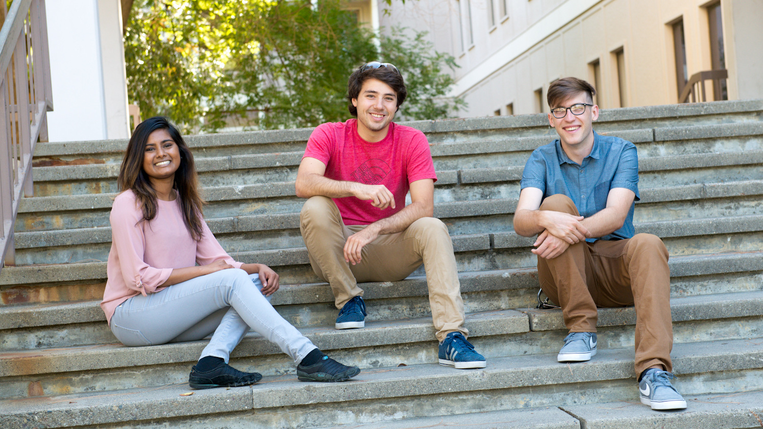 Three graduate students sitting on the steps of the Chemistry Building