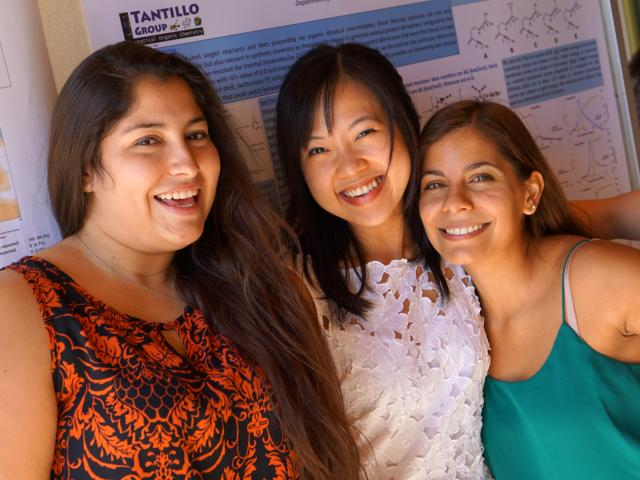 Three graduate students standing in front of a scientific poster. (PC: Minh Hoang)